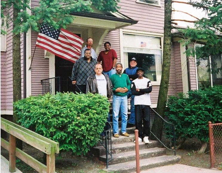 "Oxford House residents stand outside their home. Used with permission from the author. Photo previously published in ""Communal Housing Settings Enhance Substance Abuse Recovery"" by Jason, L. A., Olson, B. D., Ferrari, J. R., & Lo Sasso, A. T. (2006). American Journal of Public Health, 91, 1727-1729. PMCID: PMC1586125."