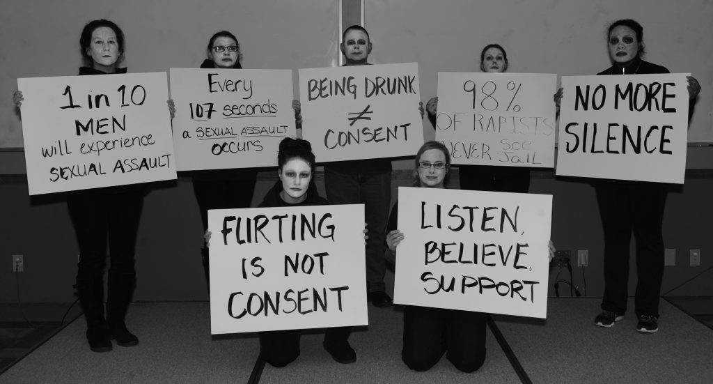 Photograph of people holding sexual assault awareness signs.