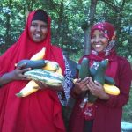 Photograph of two women holding produce