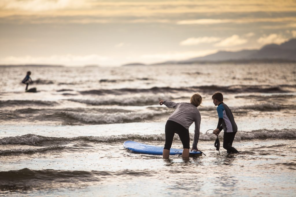 Photograph of two people surfing