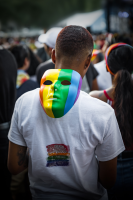 Photograph of a man with an LGBTQI-themed mask around his neck