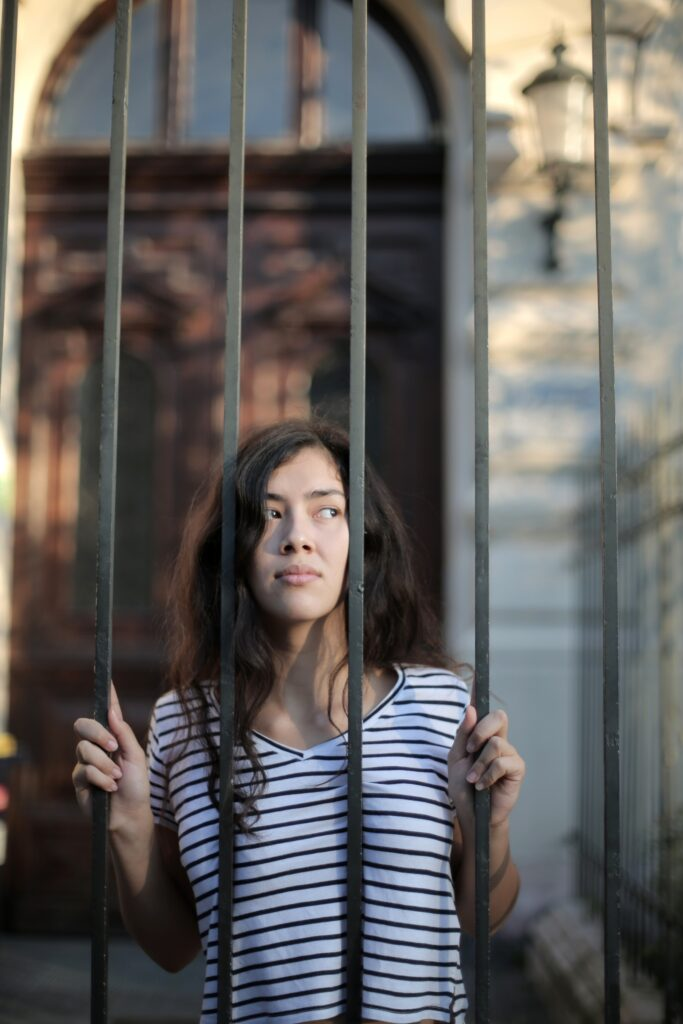 Photograph of a girl behind prison bars