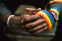 Photograph of hands holding LGBT ribbon