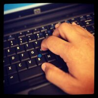 Photograph of hands on a computer